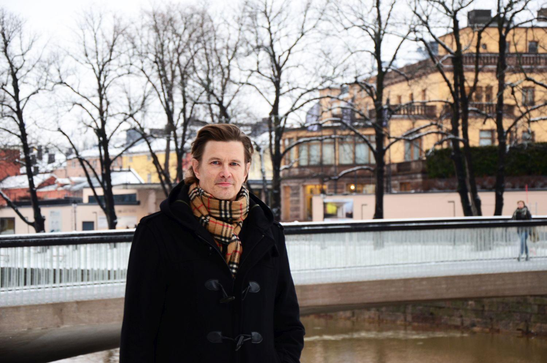 Man i svart kappa vid åstranden i Åbo.