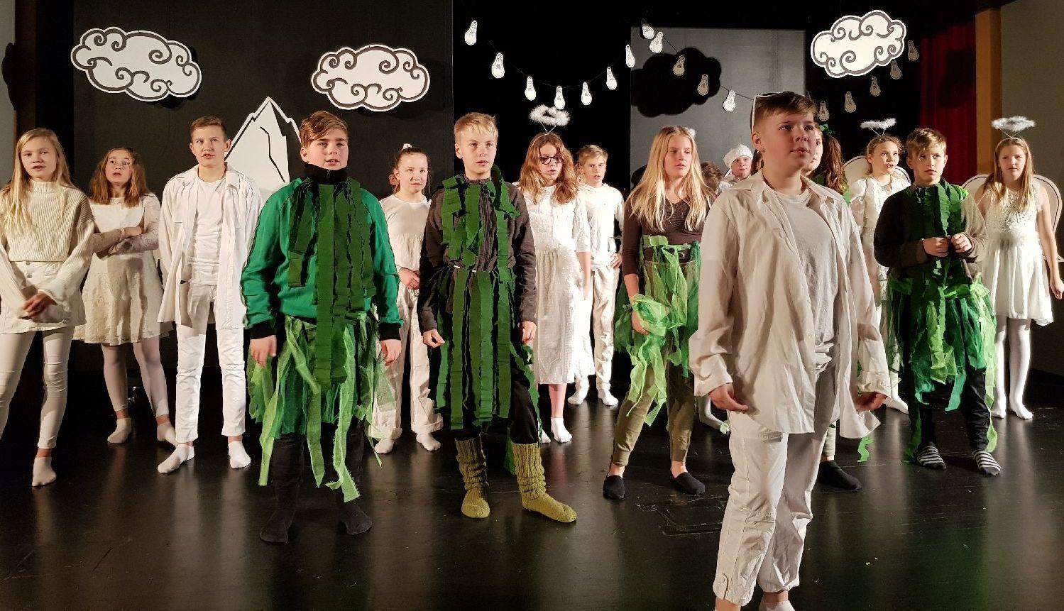 Teatergäng på scenen i vita och gröna kläder
