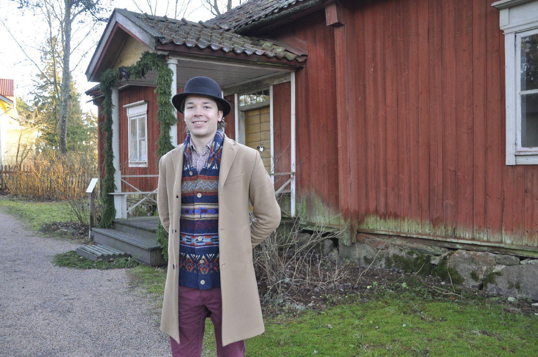 Ung man i hatt framför en gammal träbyggnad.
