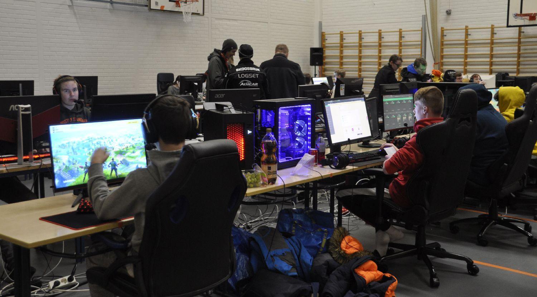 Datorskärmar och spelande ungdomar i en stor sal