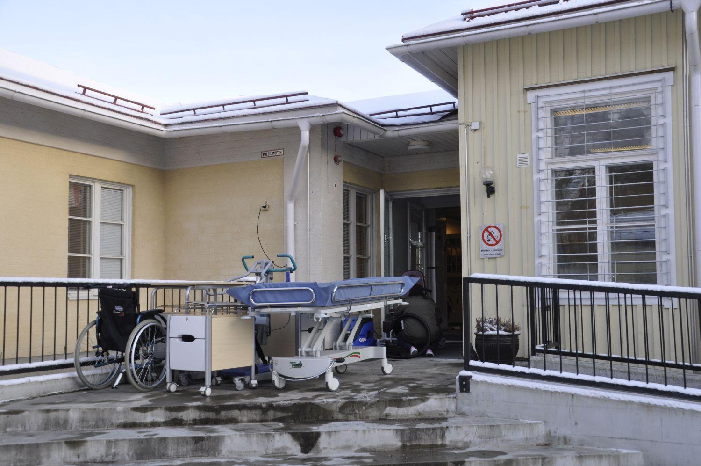 Trappan till en vårdfastighet. Här står en säng, en rullstol och lite andra grejer.