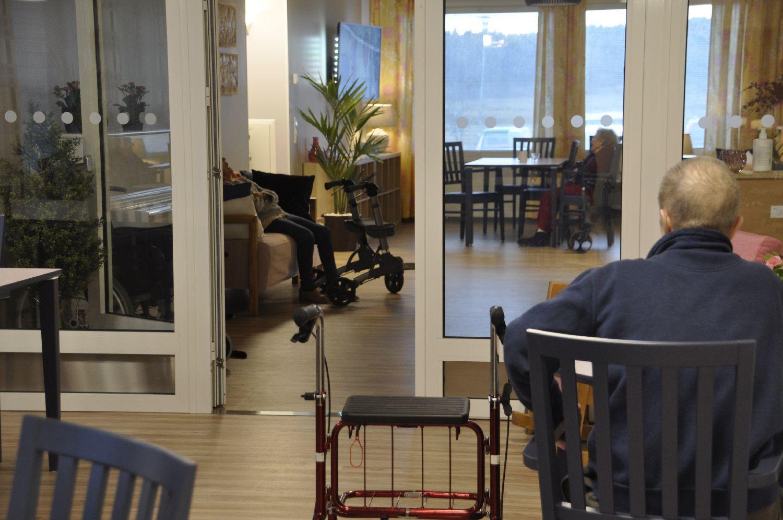 Två stora rum i ett äldreboende. Glasdörr skiljer dem åt. Äldre man och hans rollator syns bakifrån