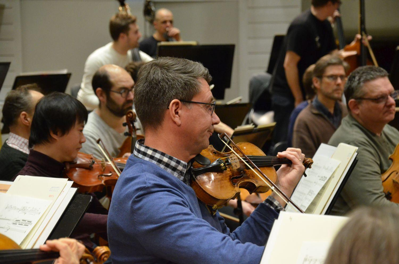Man som spelar violin i en orkester.