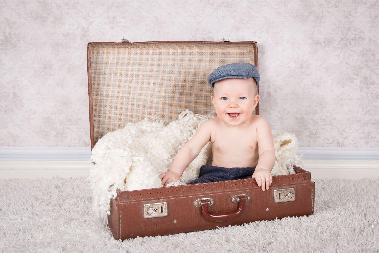 Litet barn sitter i en kappsäck. Fotostudiofoto.