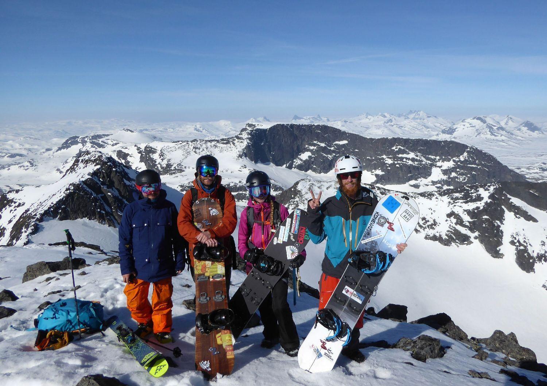 Fyra snowboardare på ett berg. Bakom syns snötäckta berg.
