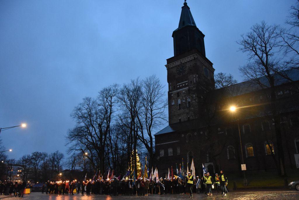 Domkyrkan i Åbo avtecknas mot en mörkblå himmel. Intill kyrkan står en hop människor med fanor i händerna samlade.