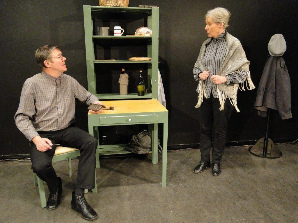 En teaterscen där en man som sitter på en stol och en kvinna som står upp pratar med varandra i ett enkelt kök.