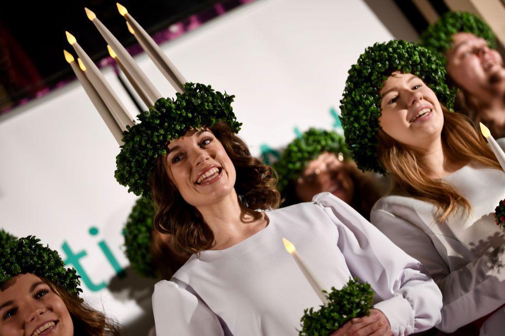 Finlands lucia 2019 Sara Ray sjöng för publiken i Forum på luciamorgonen. Här är hon med ljus i hår och vit klänning.