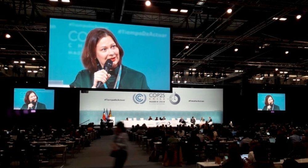 Kvinnas ansikte på stor skärm i konferenssal.