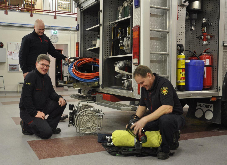 Tre brandmän grejar med utrustning vid en brandbil inne i en brandstation.