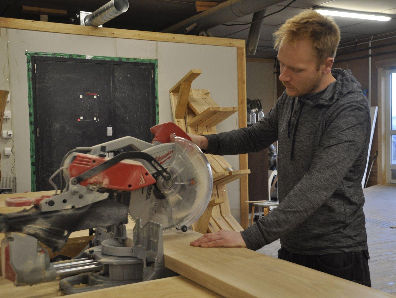 Man vid ett sågverktyg i ett snickeri.