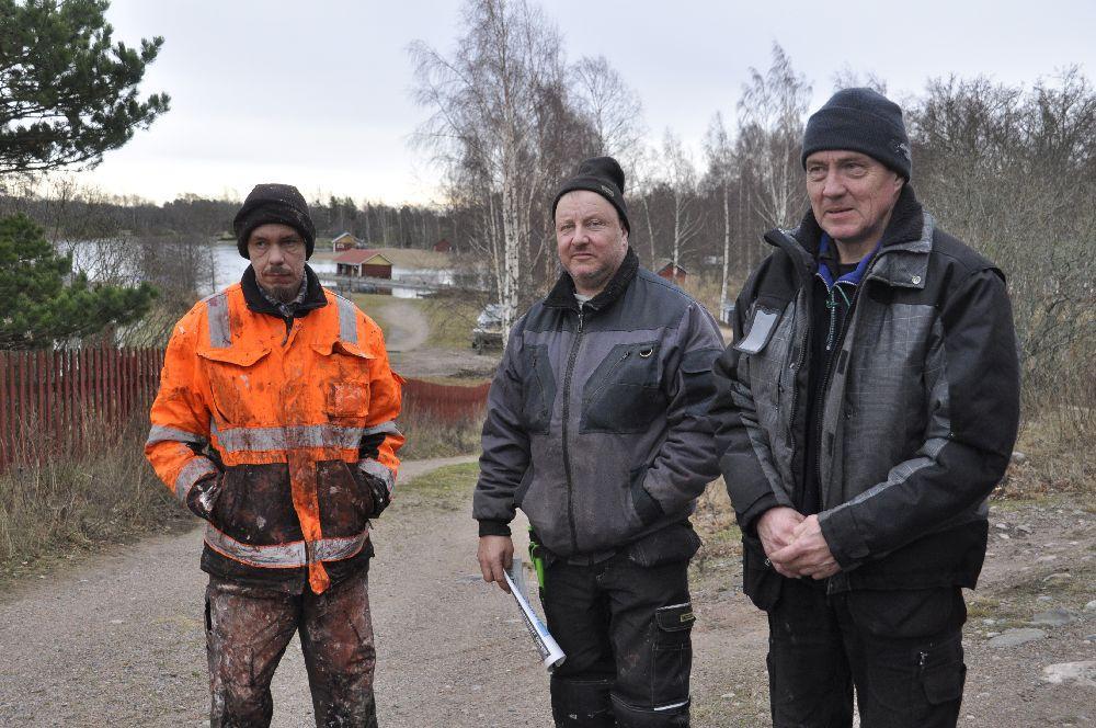 Tre män i arbetskläder utomhus.