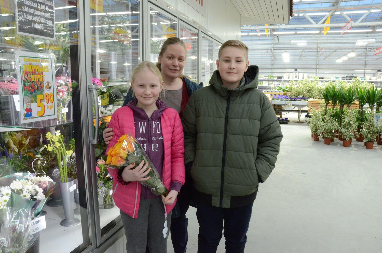 Mamma och två barn med en bukett rosor.