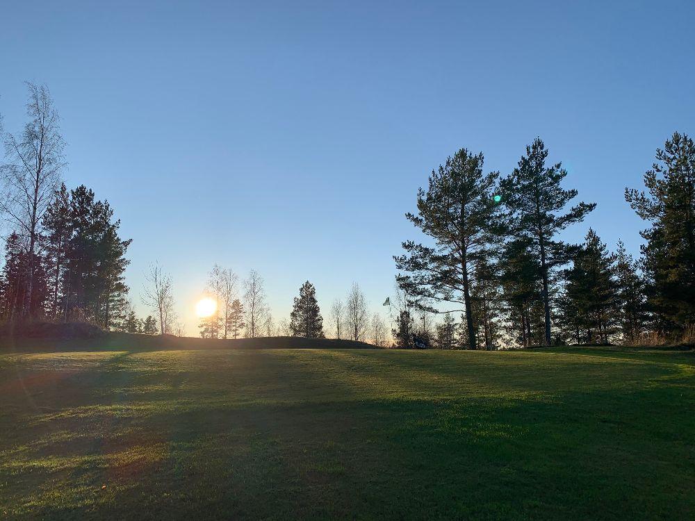 En grön backe av en golfbana, där solen tittar fram