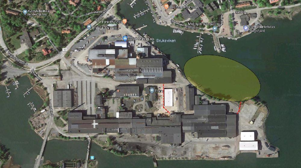 Flygfoto av ett industriområde med stora byggnader. I viken intill är ett stort område färgat i grönt