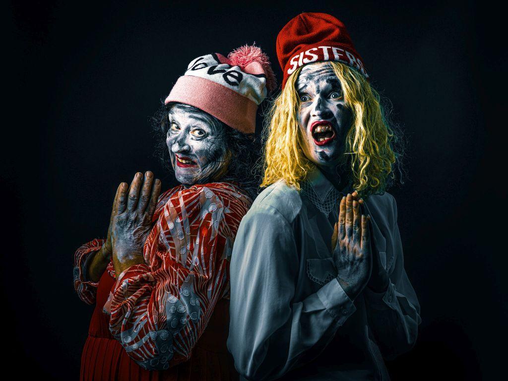 Två sjabbiga kvinnor klädda i vintage blusar och moderna skidmössor målade med stora mängder grå ansiktsfärg står rygg i rygg och håller händerna med handflatorna tryckta emot varandra som i bön.