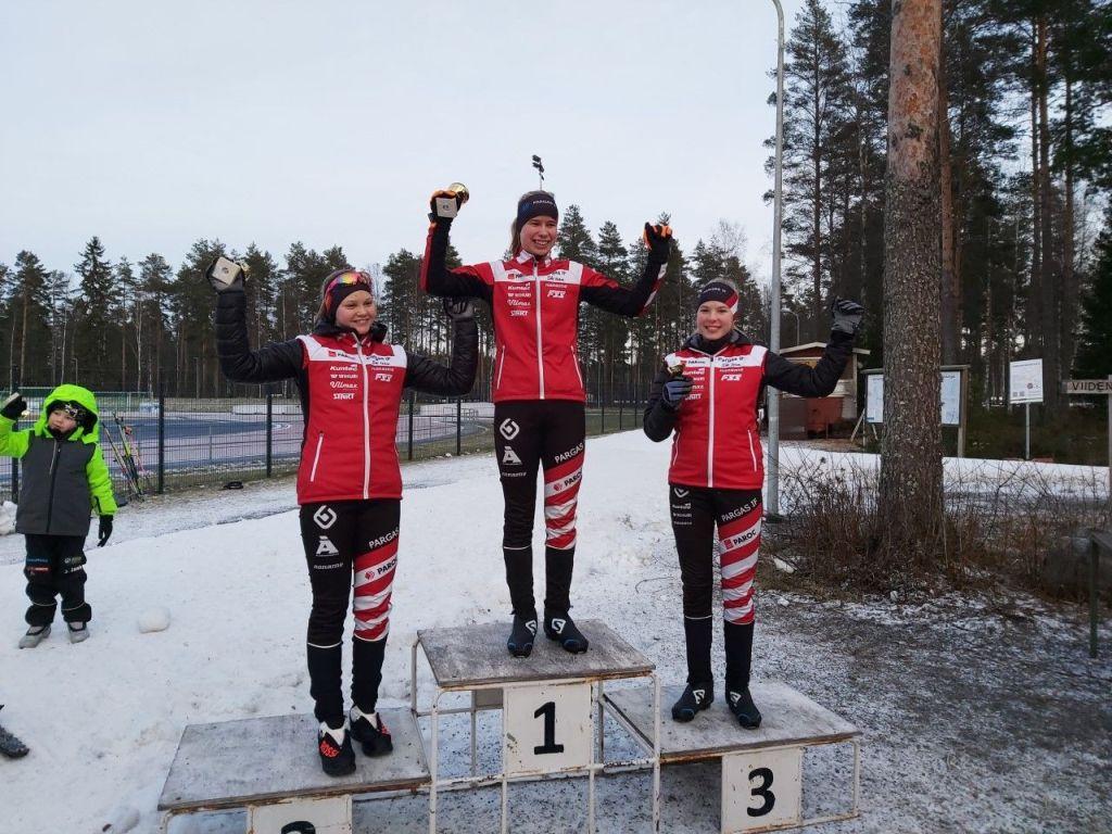 Tre skidåkare med medaljer