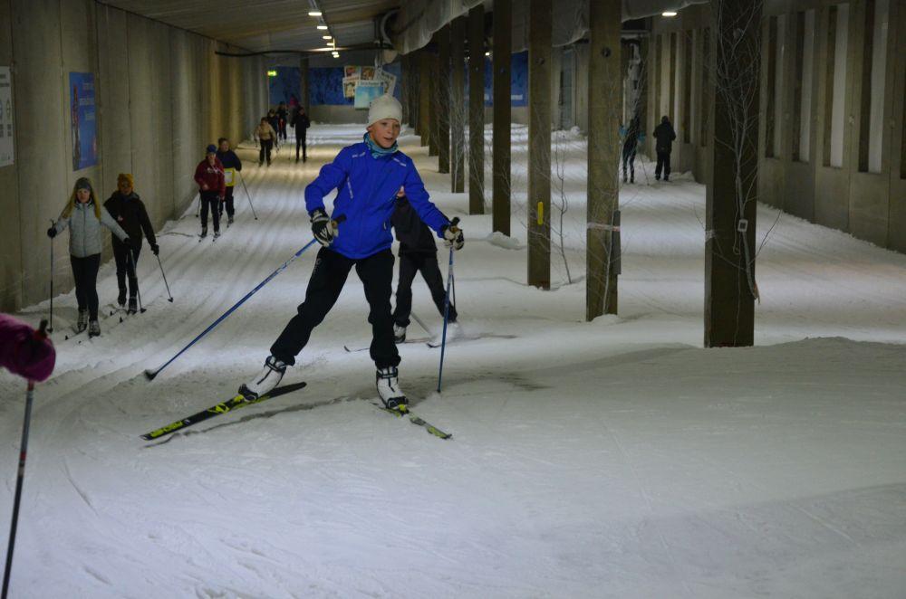 En vit pojke klädd i blått åker skidor längs ett inomhusskidspår