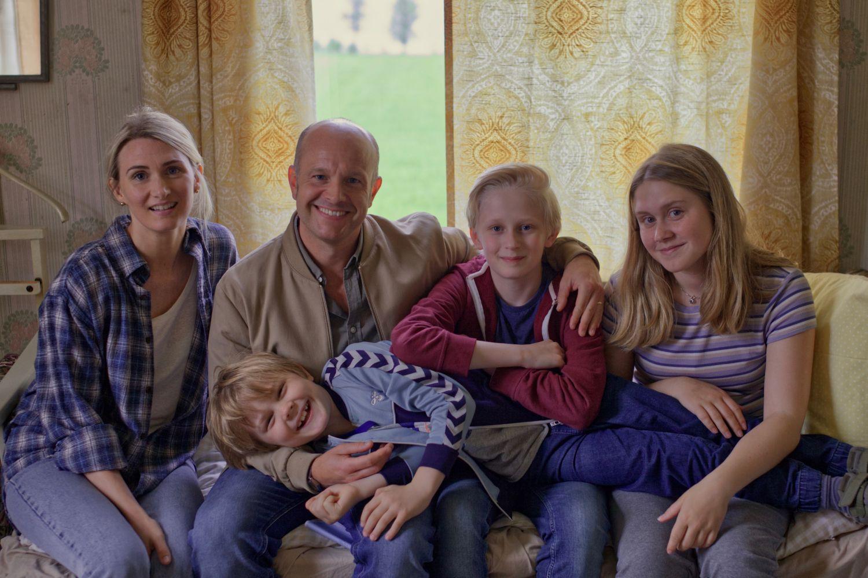 Man och kvinne med tre barn sitter i en soffa.