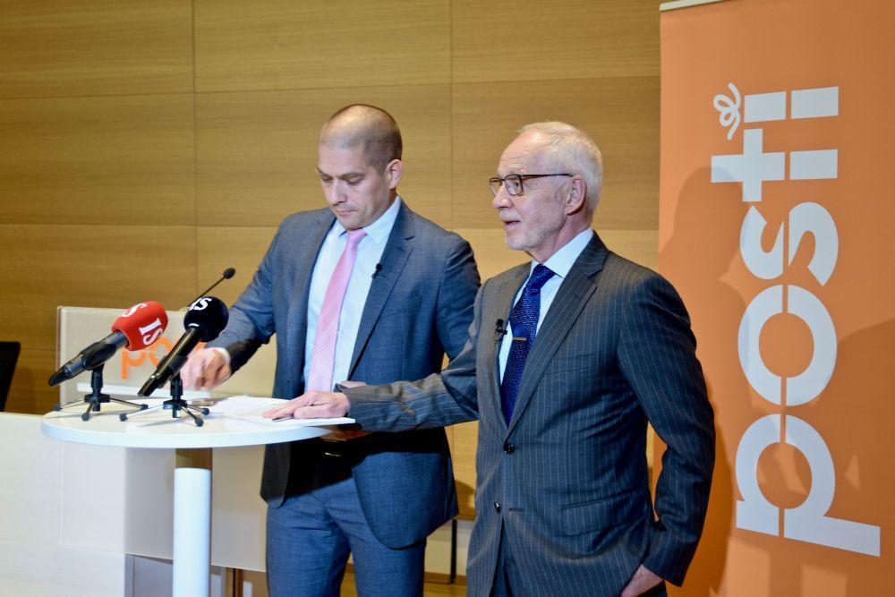 Två män vid mikrofoner och en Posti-banderoll