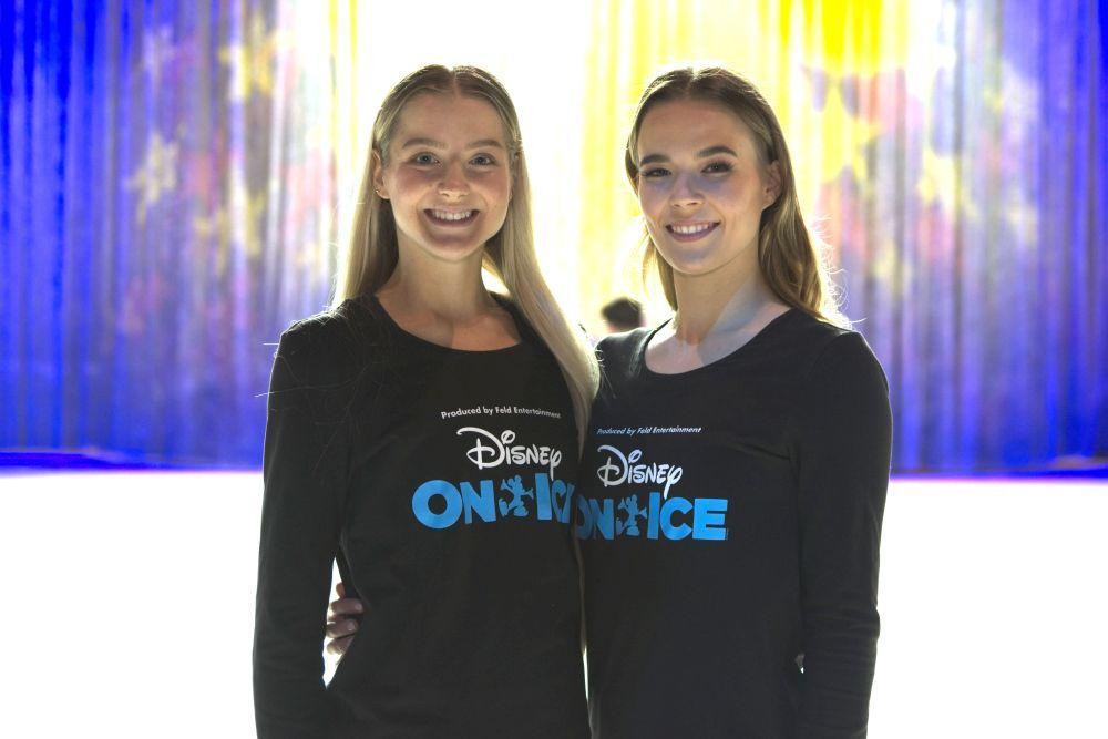 Två flickor står bredvid varandra.