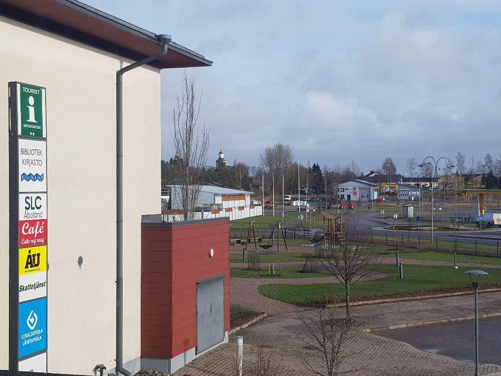 Fotot taget snett uppifrån. En husvägg syns, en innergård, och en park.
