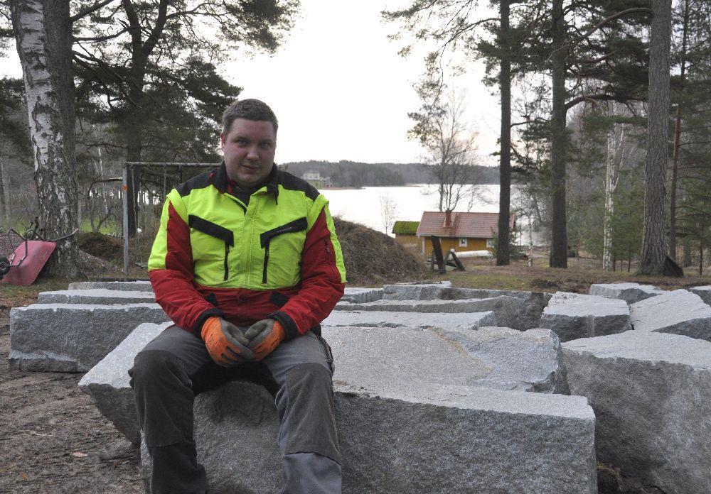 Man i arbetskläder sitter på granitblock.