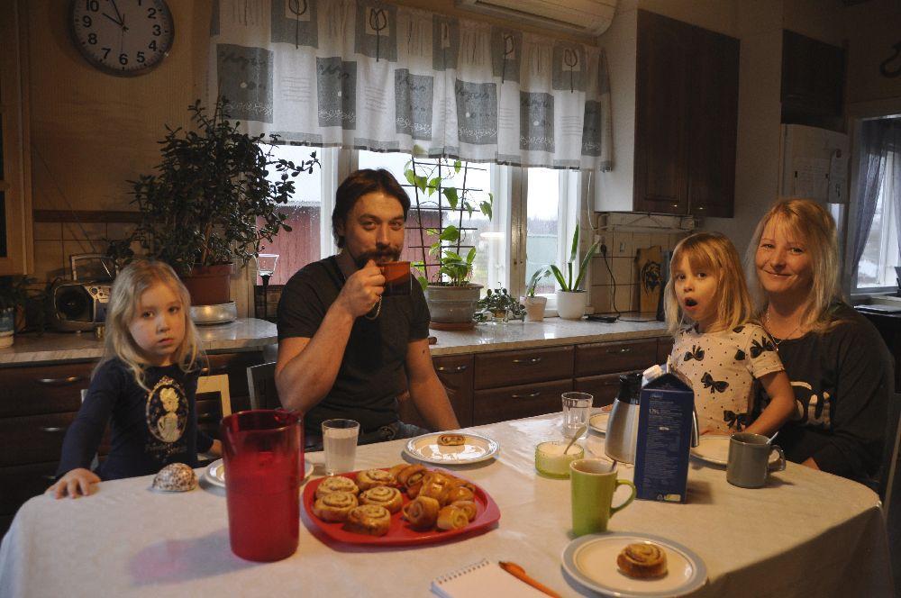 Familj dricker kaffe/saft och äter bulle i ett kök. Ett reporterblock syns på bordet