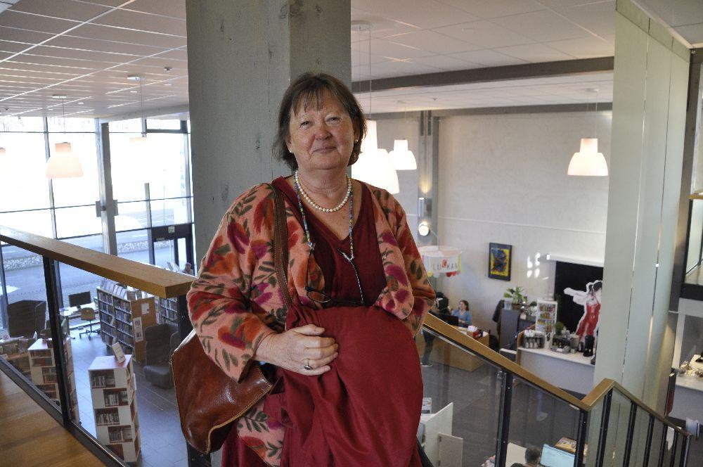 Kvinna med ett café och ett bibliotek i bakgrunden.