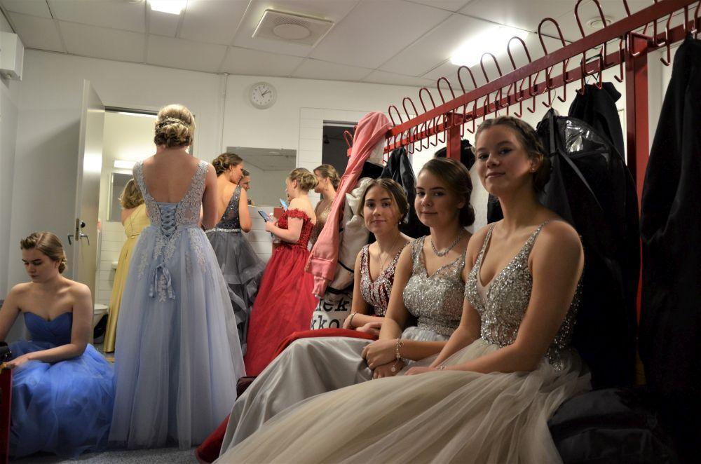 Flickor i finklänningar i ett omklädningsrum.