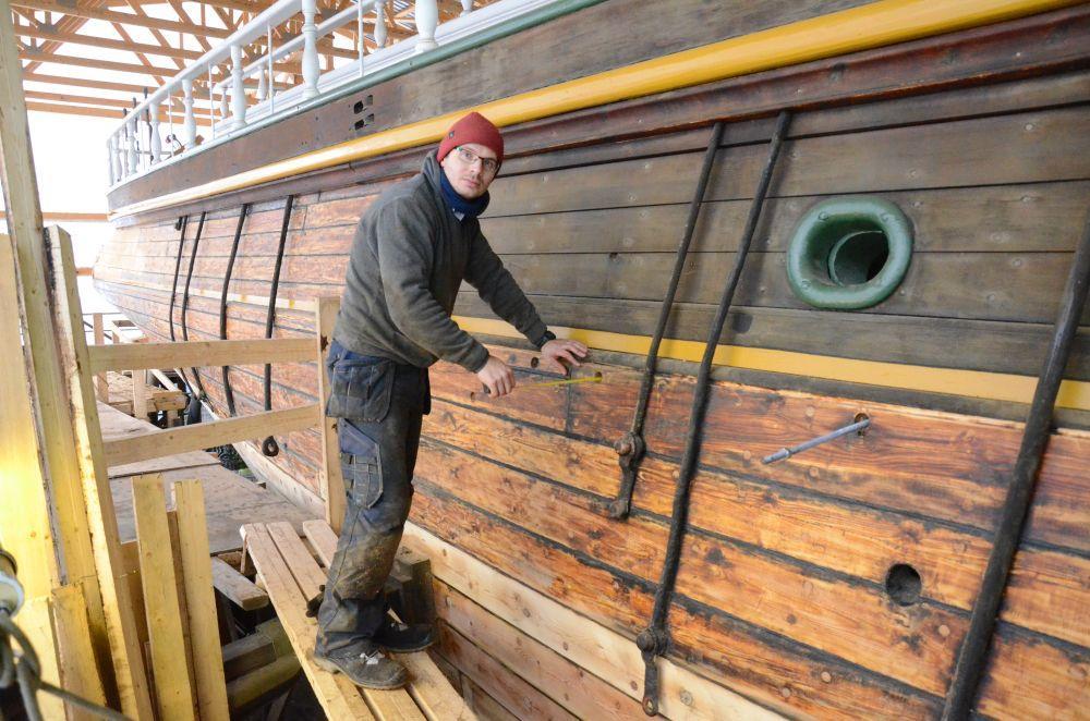Ung man jobbar på utsidan av ett gammalt fartyg.