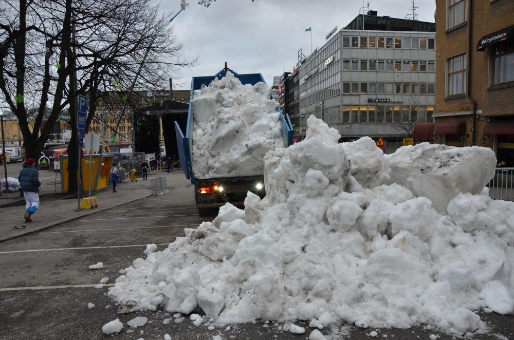 Lastbil kippar snö.