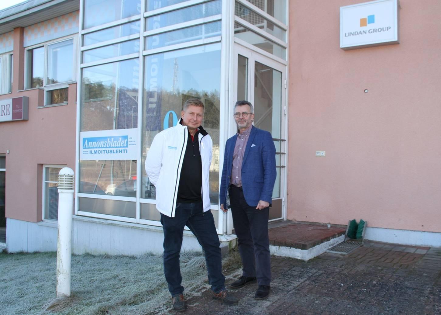 två män vid en husvägg i samband med ett företagsköp