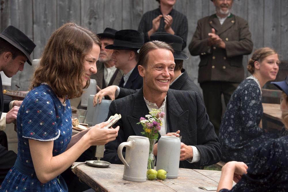 Kvinna och man sitter vid bord, scen ut film