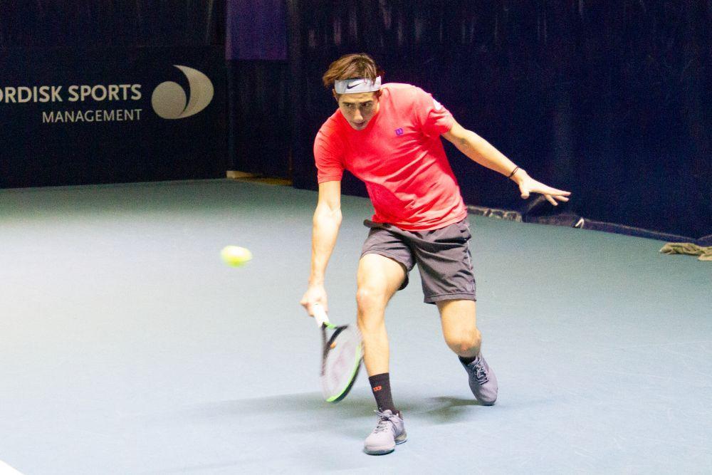Yngling spelar tennis