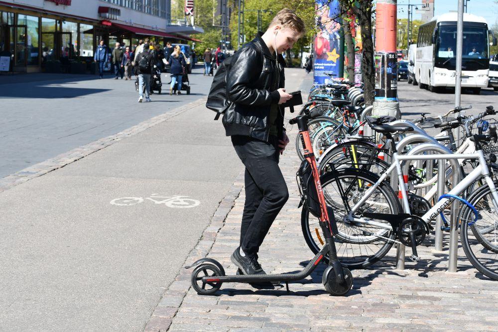Ung mananvända en elsparkcykel. står i beråd att