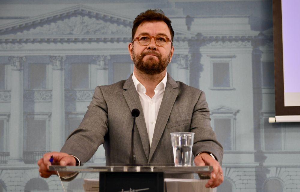 Man med glasögon står vid ett podium.