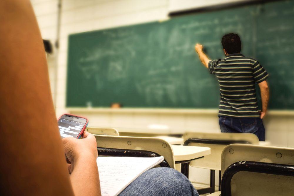 En person undervisar vid svarta tavlan och en annan följer med.