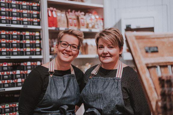Två leende kvinnor i förkläden.