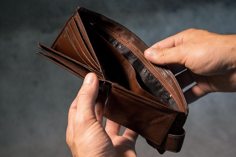Händer som håller i en plånbok.