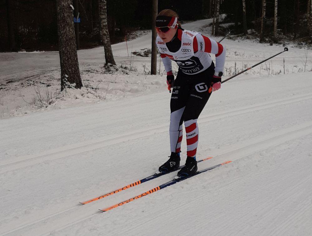 Ung kvinna åker skidor.