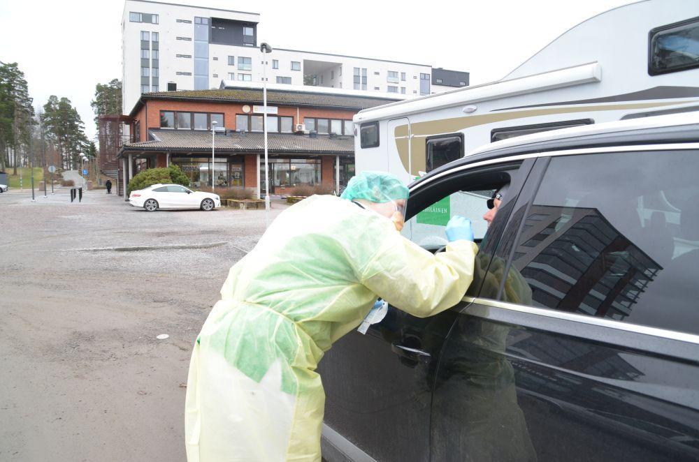 Laboratorieskötare i skyddsutrustning testar en kund som sitter i en bil.