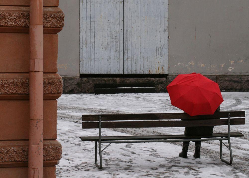 Människa sitter på parkbänk på vintrig innergård