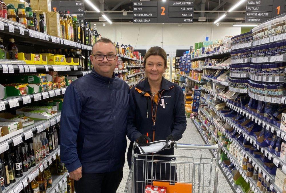 Man och kvinna mellan butikshyllor