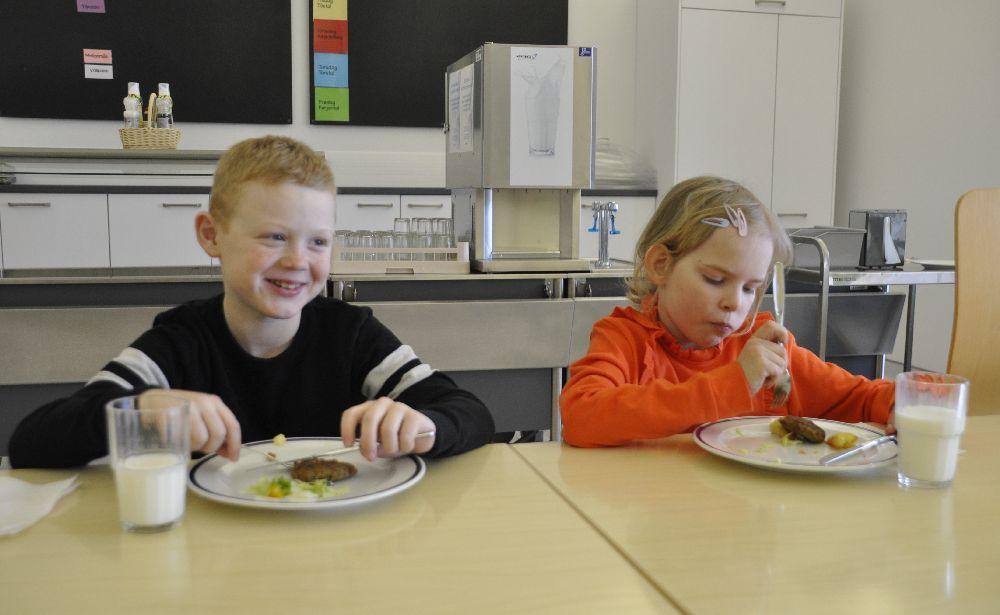 Två skolbarn sitter och äter i en skolmatsal.