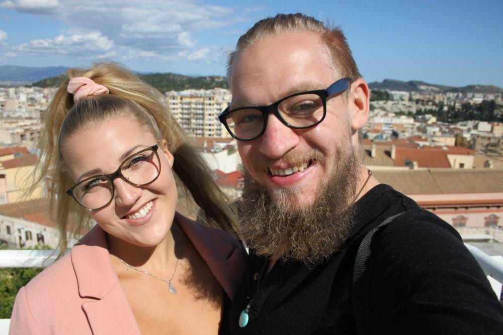 En kvinna och en man med en stad i bakgrunden.