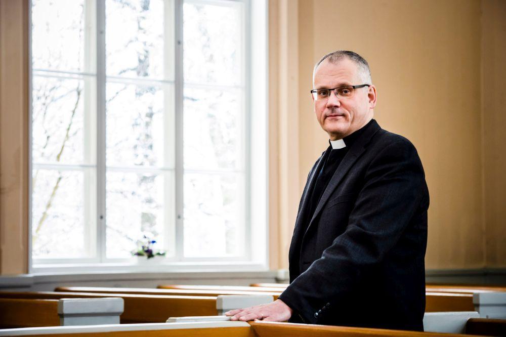 Präst står vid kyrkfönster