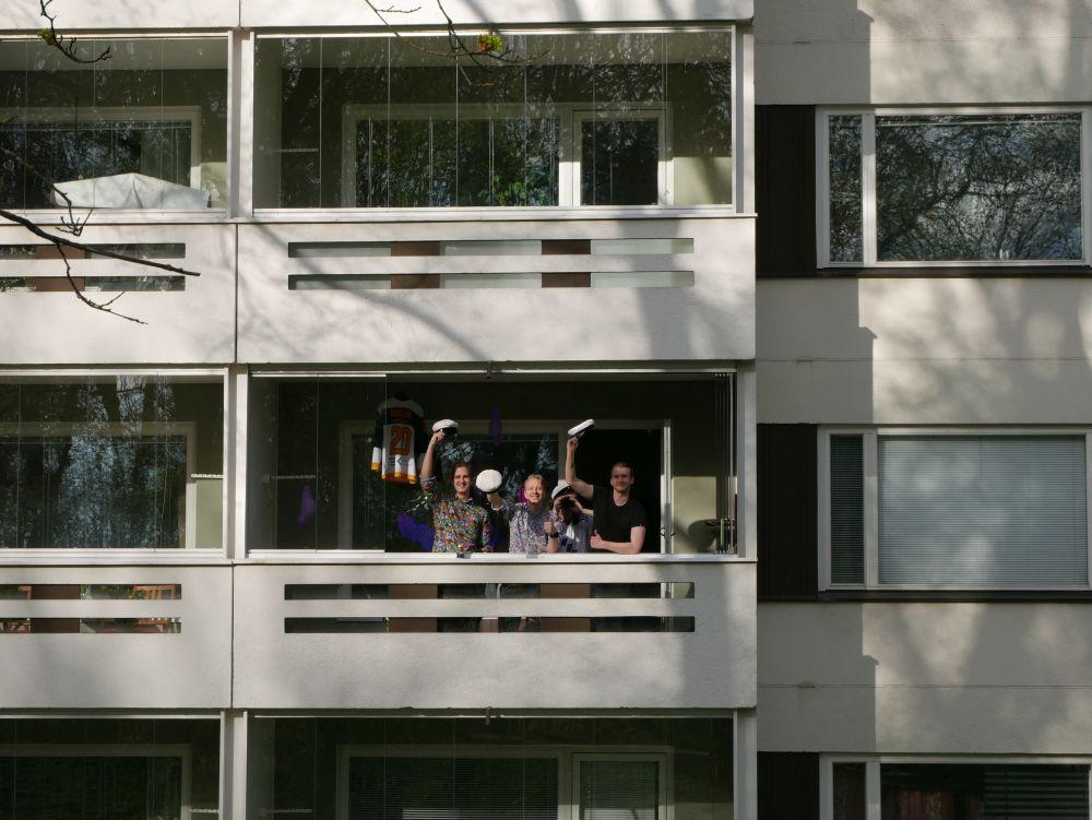 Fyra män viftar med studentmössor från en balkong