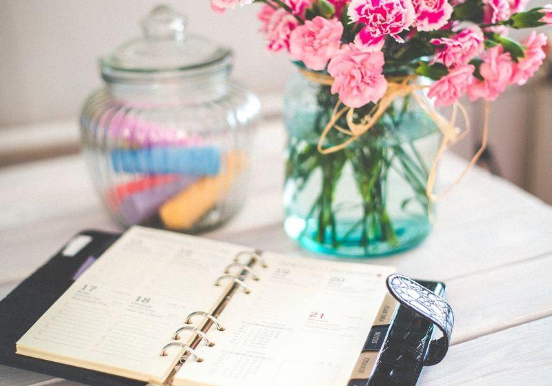 Kalender på bord med blomvas