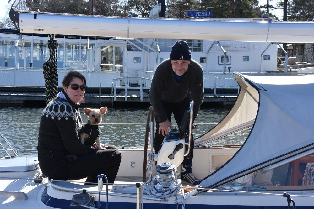 En kvinna, en man och en liten hund på en segelbåt.